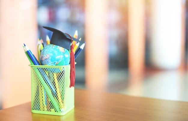 Apprendimento dell'istruzione e ritorno a scuola con il cappello di laurea su un astuccio sul tavolo in biblioteca - cappello di laurea sul concetto di studio di educazione globale modello globo terrestre