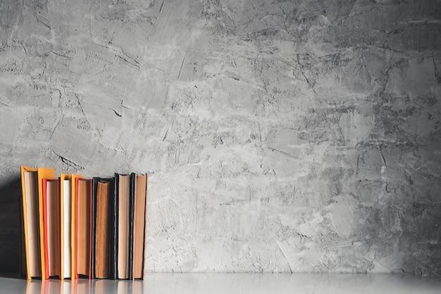 Concetto di educazione e lettura - gruppo di libri colorati sul tavolo bianco su sfondo grigio