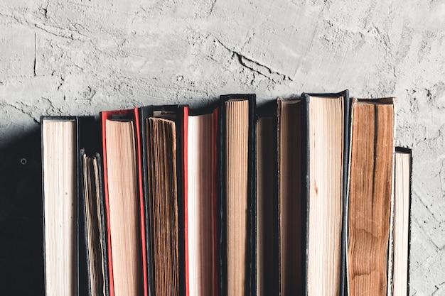 Concetto di educazione e lettura, gruppo di vecchi libri colorati sul tavolo bianco su sfondo grigio