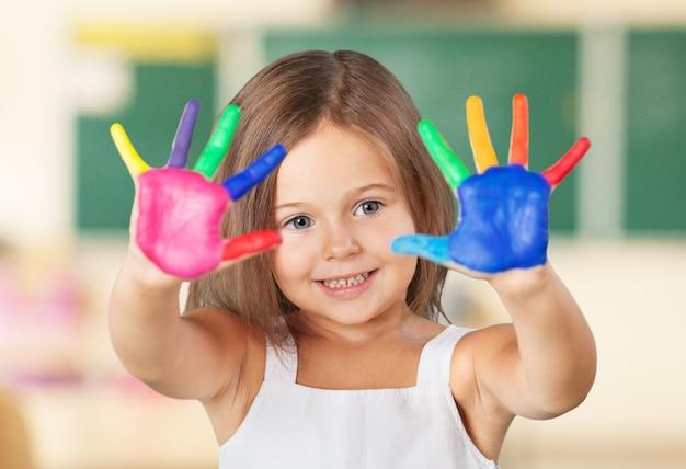 Educazione, scuola, arte e concetto di pittura - piccola studentessa che mostra le mani dipinte a scuola