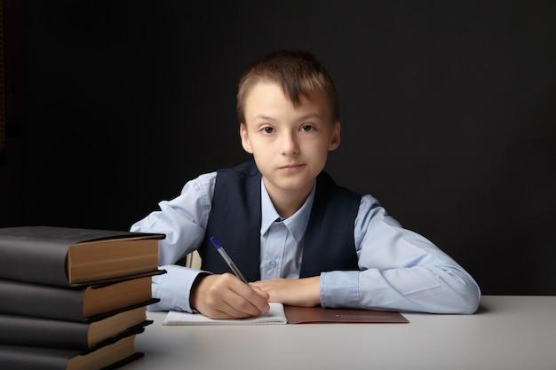 Istruzione al concetto di scuola. ragazzo seduto al tavolo e studiando isolato nell'aula grigia.