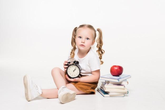 Istruzione e concetto di scuola. bambina sorridente dell'allievo con l'orologio del libro e la mela che si trovano sul pavimento