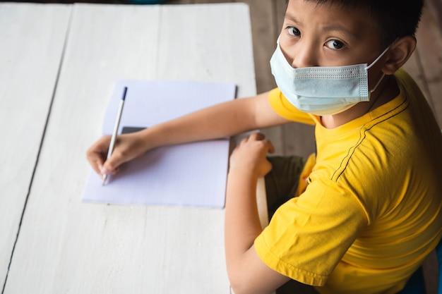 Concetto di educazione, scuola e pandemia - ragazzo studente che indossa maschera medica protettiva per il viso