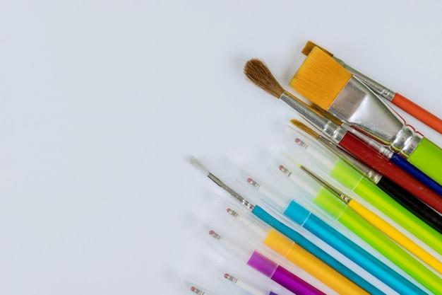 Tempo di istruzione una cancelleria di colore diverso in stand su una varietà di materiale scolastico