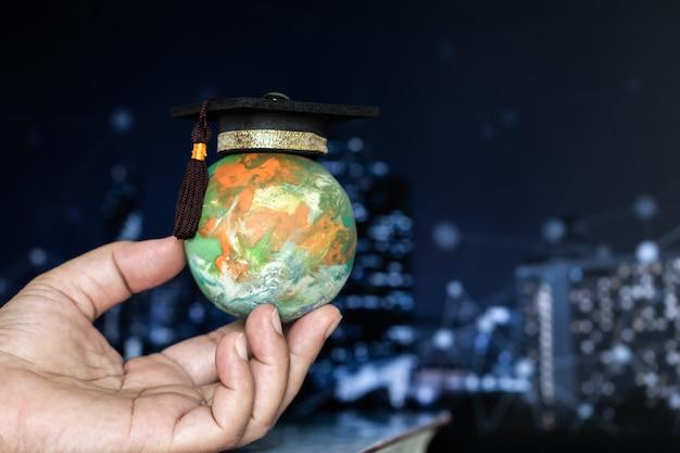Idee per la conoscenza del mondo dell'istruzione. tappo di laurea su uomo d'affari che tiene i modelli globo terrestre nelle mani su sfocatura grafica hud sfondo rete città ioc. concetto di studio aziendale globale all'estero educativo