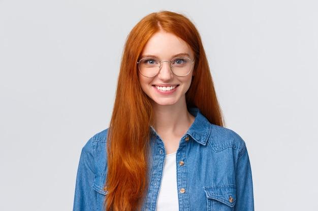 Concetto di educazione, gioventù e corsi. close-up allegra ragazza rossa carismatica adolescente, studente di college con gli occhiali, sorridente e guardando determinato, a partire dal nuovo anno scolastico, sfondo bianco.