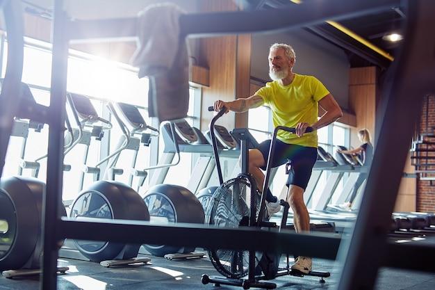 Efficace macchina cardio per tutta la lunghezza di un uomo atletico maturo in abbigliamento sportivo che fa ciclismo su
