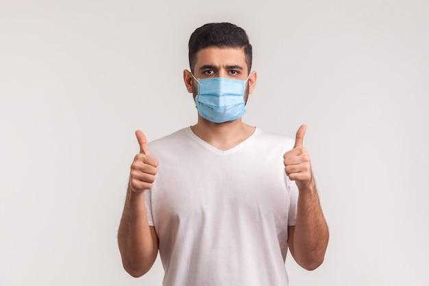 Protezione efficace contro le malattie contagiose. uomo che mostra i pollici in su e indossa una maschera igienica