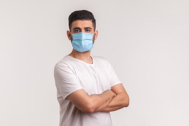 Protezione efficace contro il coronavirus. uomo che tiene le mani incrociate e indossa una maschera igienica