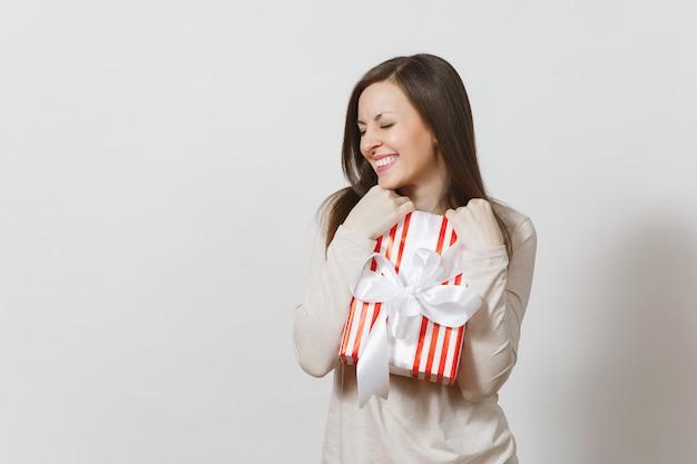 Donna efficace che abbraccia la scatola attuale a strisce rosse con il nastro, arco isolato su fondo bianco. per la pubblicità. san valentino, giornata internazionale della donna, natale, compleanno, concetto di vacanza.