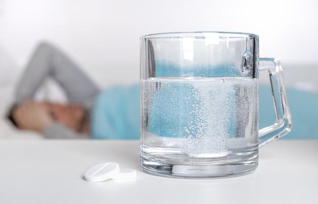 Compressa effervescente che cade nel bicchiere e un uomo malato con il virus covid-19