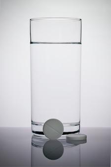 Compresse effervescenti e un bicchiere d'acqua