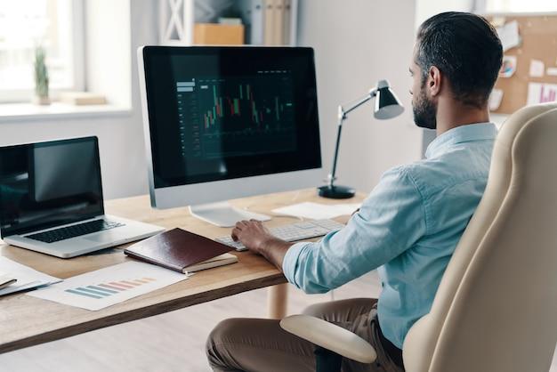Efficienza. giovane uomo d'affari moderno che analizza i dati utilizzando il computer mentre è seduto in ufficio