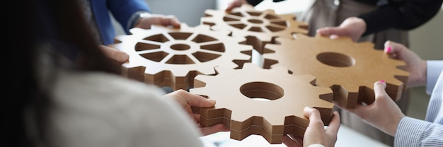 Un efficiente team aziendale collega gli ingranaggi in legno in uno