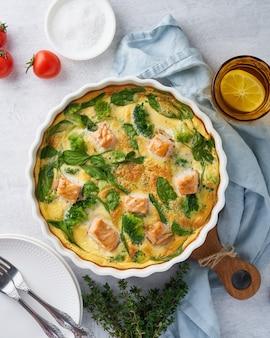 Frittata all'uovo, frittata con salmone, broccoli e spinaci. piatto italiano, quiche senza crosta con uova, pesce e verdure. dieta salutare chetogenica mediterranea. vista dall'alto, verticale