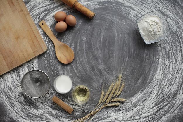 Uovo, farina, olio d'oliva, latte, spighe di grano, utensile da cucina su sfondo grigio tavolo.