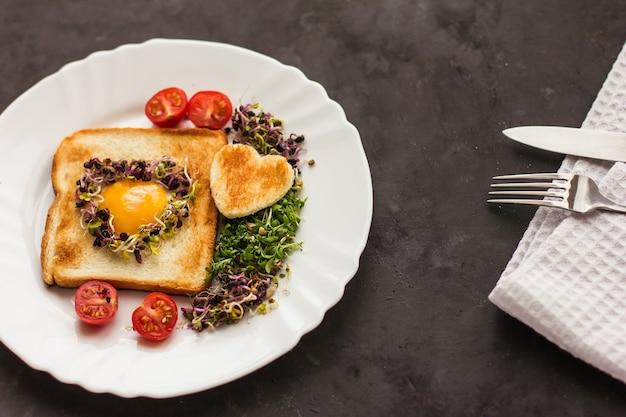 Uovo in un buco di pane a forma di cuore, microgreens, cibo sano colazione, tè, sfondo nero