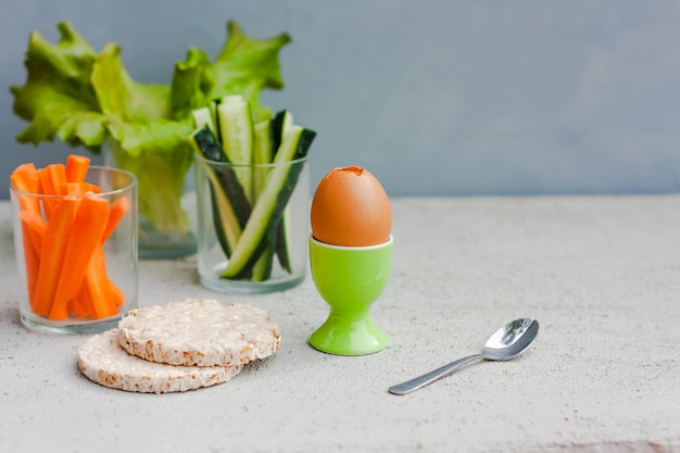 Uova, lattuga, cetrioli e carote servite in una tazza di vetro come spuntino. colazione salutare.