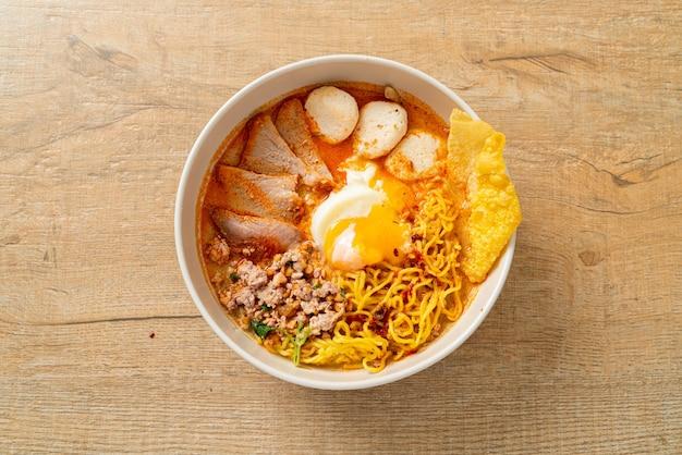 Tagliatelle all'uovo con maiale e polpette in zuppa piccante o tom yum noodles in stile asiatico