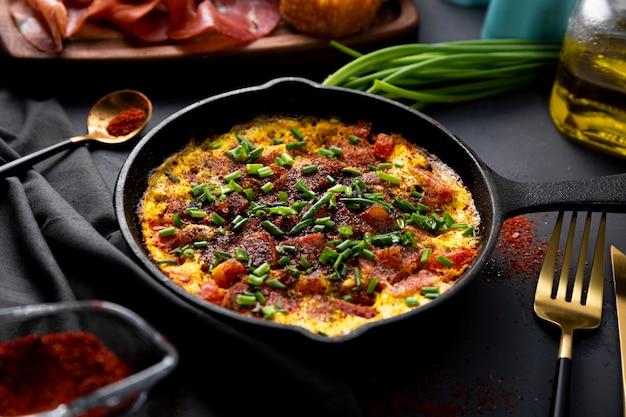 Frittata di uova con salsiccia e condimenti in una padella di ghisa da vicino, messa a fuoco morbida.
