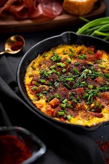 Frittata di uova con salsiccia e condimenti in una padella in ghisa da vicino, foto verticale con messa a fuoco morbida.