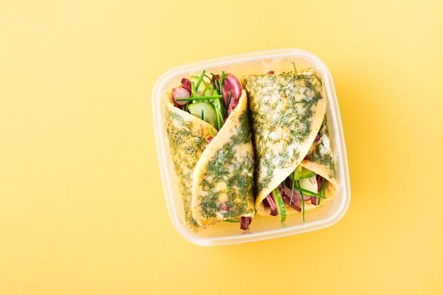 Involtini di uova ripieni di pastrami, verdure e cipolle verdi in una scatola su un tavolo giallo. da asporto, colazione a scuola