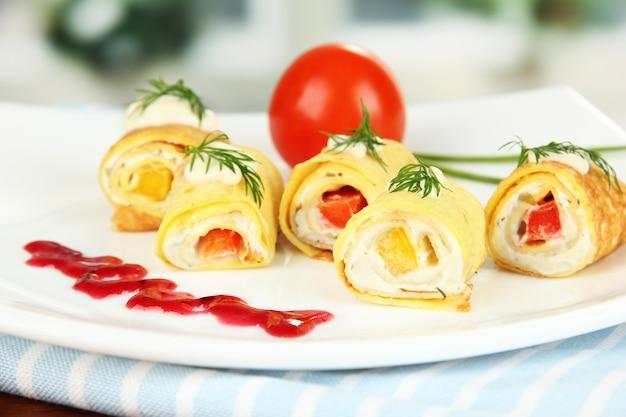 Involtini di uova con crema di formaggio e paprika, sul piatto, su brillante