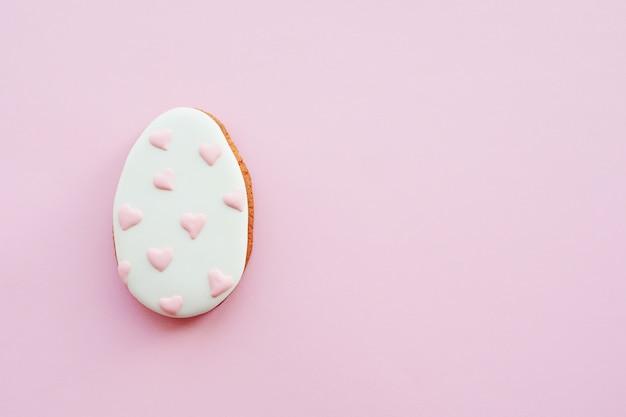 Pan di zenzero a forma di uovo con cuori rosa dipinti. concetto di pasqua. minimalismo.