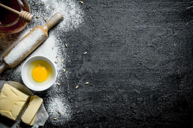 Uovo con miele e burro. su sfondo nero rustico