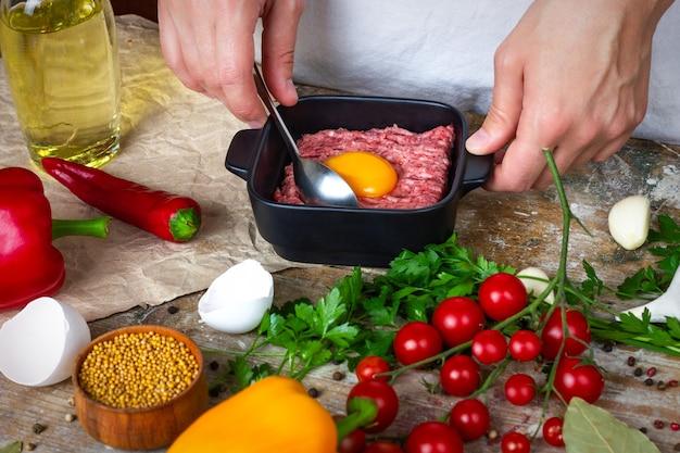 Tuorlo d'uovo su carne di maiale macinata in un piatto nero su un tavolo di legno con pomodorini aglio spezie e mu...