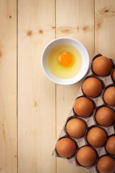 Tuorlo d'uovo in una piccola ciotola con uovo fresco in scatola di carta. ingrediente alimentare per proteine elevate.