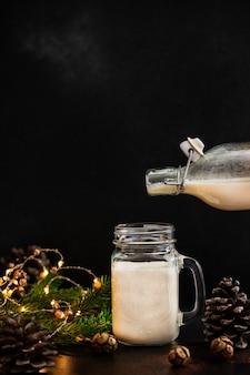 Bevanda alcolica di natale tradizionale dello zabaione con cannella e noce moscata. zabaione che versa da una bottiglia in un barattolo. umore vacanze invernali. sfondo scuro