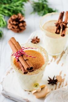 Frullato di bevanda natalizia tradizionale allo zabaione con cannella su sfondo chiaro vecchio