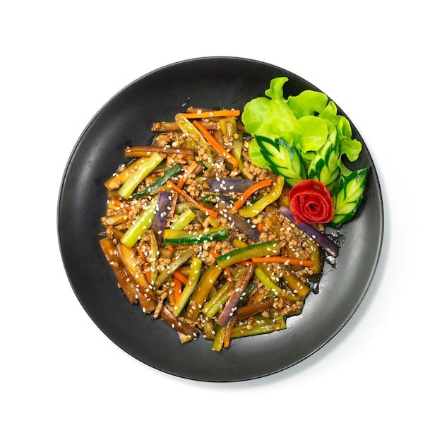 Melanzane saltate in padella con salsa giapponese di maiale macinata decorare la vista dall'alto di verdure intagliate