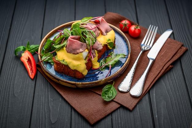 Uova alla benedict su pane tostato con prosciutto e salsa. prima colazione al ristorante