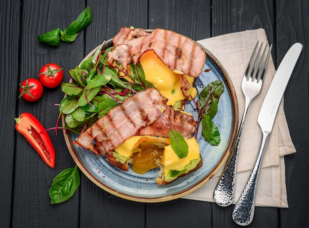 Uova tostate alla benedict, bacon, uova in camicia e deliziosa salsa olandese burrosa. un ristorante