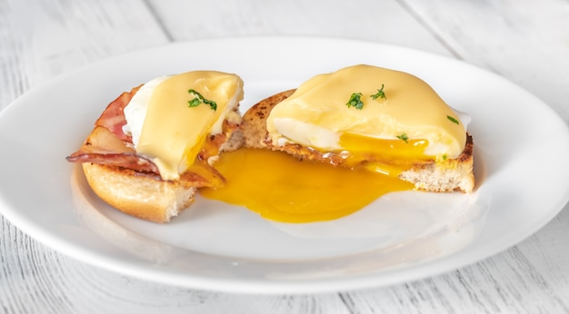 Benedict delle uova con pancetta affumicata sulla zolla bianca