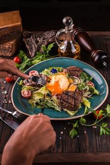 Benedict delle uova con carne di manzo su un grande piatto bianco