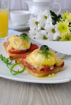 Uova benedict con prosciutto e pomodoro e formaggio su pane tostato con succo d'arancia e caffè