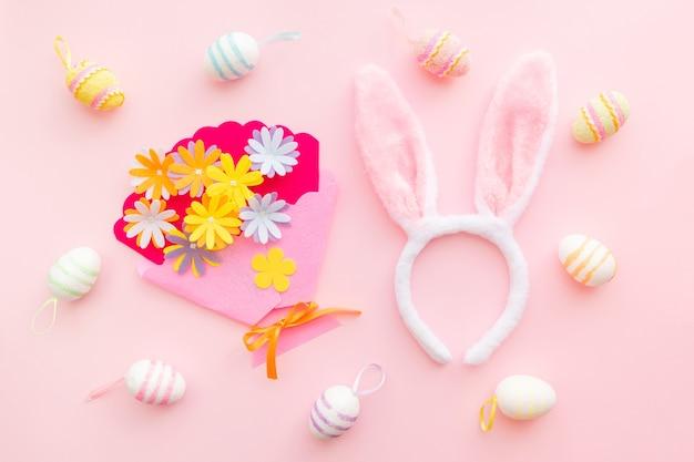 Uova e fiori artigianali su sfondo rosa il giorno di pasqua. celebrare la pasqua in primavera. vista dall'alto