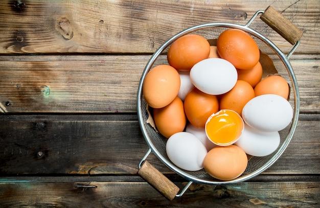 Uova in una casseruola su un tavolo di legno.