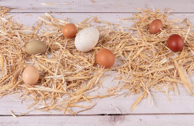 Uova di varie dimensioni e colori con paglia su un tavolo di legno