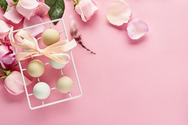 Uova in supporto in ceramica bianca e fiori su fondo rosa. vista dall'alto.