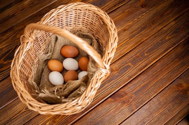 Uova in un cesto di vimini su un vecchio tavolo in legno vintage, cucina rustica o rustica ancora in vita.