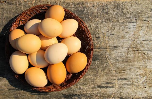 Uova in cesto di vimini su tavola di legno