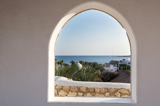 Egitto. uno sguardo attraverso la cornice sulle palme. bella vista. casa bianca e veranda con vista sul mare e sulle palme. vista mare dalla camera