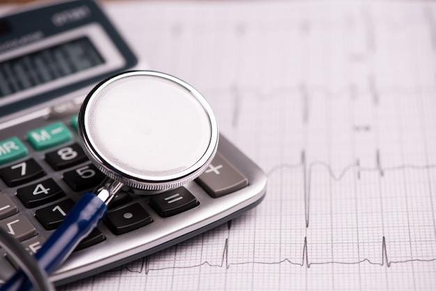 Ecg con stetoscopio e calcolatrice che mostra il costo dell'assistenza sanitaria. avvicinamento