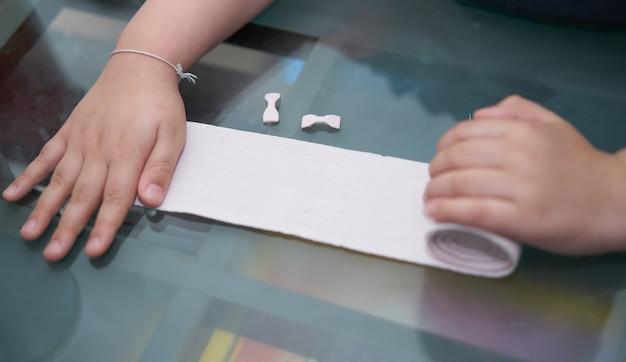 Benda di garza elastica in rotolo tenuta in mano con adesivo per la cura di impacchi di primo soccorso in caso di incidente con rilascio sul tavolo