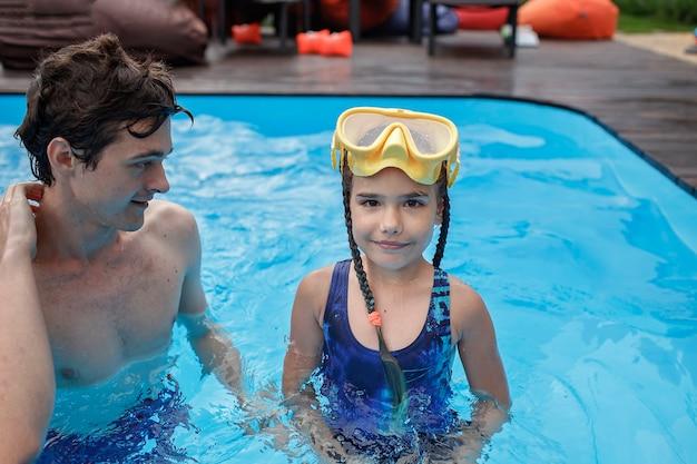 Il fratello maggiore addestra il fratellino a nuotare in piscina all'aperto durante uno stile di vita sano d'estate