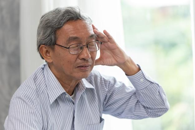 Sintomo di malattia di mal di testa anziano da indossare occhiali.